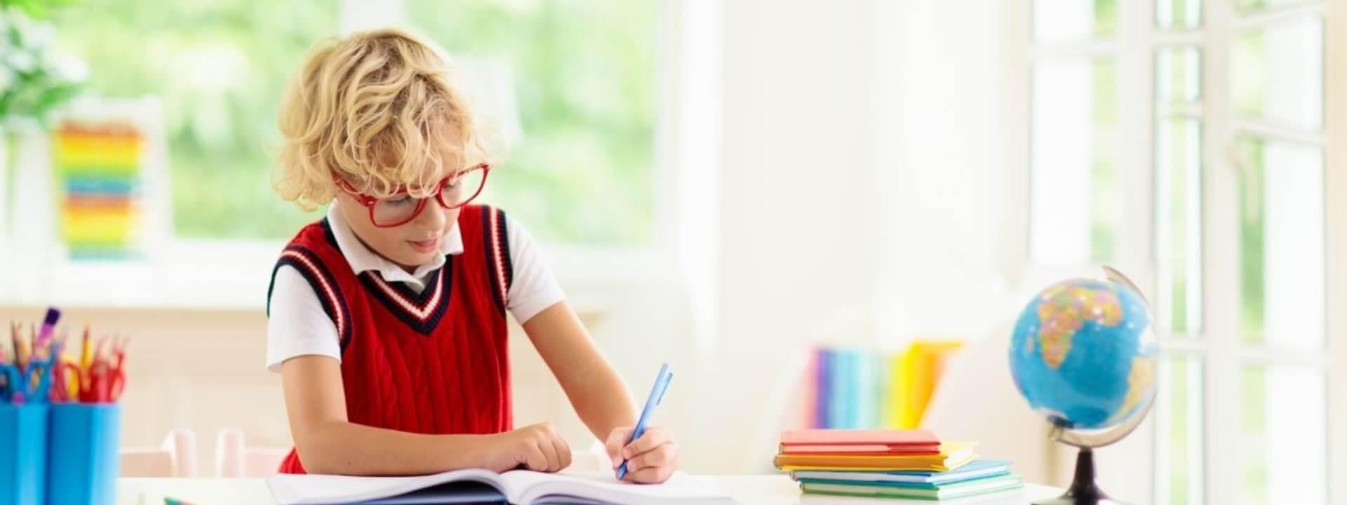 kid in eyeglasses writing